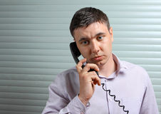 Businessman talking on telephone at office. Young businessman talking on telephone at office Stock Photography
