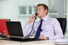 Businessman talking on telephone at office with laptop on table Stock Image