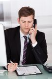 Businessman talking on telephone in office Royalty Free Stock Image