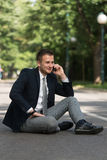 Businessman Talking On Telephone Outdoors In Park Stock Photography