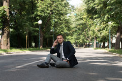 Businessman Talking On Telephone Outdoors In Park Stock Image