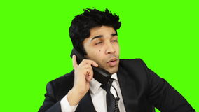 Businessman talking on telephone and showing thumbs up against green background