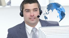 Businessman talking to clients over the internet. Close up of a Caucasian businessman talking on his headset. Beside him in the foreground is a digital animation stock footage