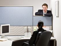 Businessman talking to co-worker. Over a cubicle Stock Photo