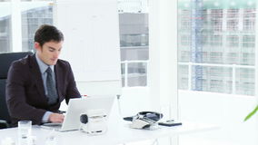 Businessman talking to his colleague in office. Panorama of businessman talking to his colleague who is using a laptop in office. Footage in high definition stock footage