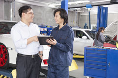 Businessman talking to Mechanic in Auto Repair Shop Royalty Free Stock Photo