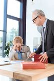 Businessman talking to overworked colleague. Mature serious businessman talking to overworked colleague at workplace Royalty Free Stock Photos