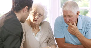 Businessman talking to senior couple. And showing sheet stock footage