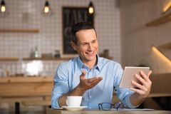 Businessman talking to somebody on videochat. Handsome businessman talking to somebody on videochat using digital tablet in cafe Stock Photos