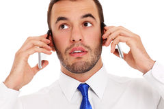 Businessman talking on two phones stock images