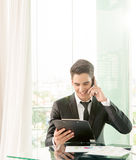 Businessman talking via cell phone in office Royalty Free Stock Photography