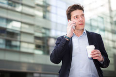 Businessman talking about work on the mobile phone. Cheerful businessman talking about work on the mobile phone at the street Royalty Free Stock Image