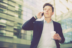 Businessman talking about work on the mobile phone. Cheerful businessman talking about work on the mobile phone at the street Royalty Free Stock Photography