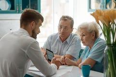 Businessman talks with elderly parents stock images