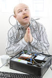 Businessman Tangled In Cables While Praying At Desk Royalty Free Stock Photo