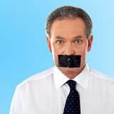 Businessman with tape on his mouth Stock Images