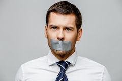 Businessman with tape sealed mouth Royalty Free Stock Photography