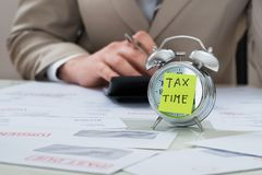 Businessman with tax time reminder note on alarm clock. Close-up Of Businessman With Tax Time Reminder Note On Alarm Clock At Desk stock image