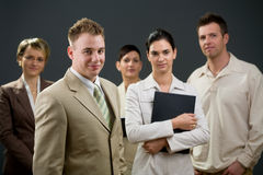 Businessman and team. Businessman standing in front of his smiling team Stock Photos