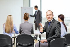 Businessman with team showing thumbs up in office Stock Image