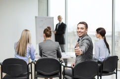 Businessman with team showing thumbs up in office Royalty Free Stock Image