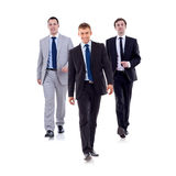 Businessman team walking. Business team walking - leadership and teamwork concepts using a group of businessmen isolated on white royalty free stock image