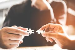 Businessman team work holding two jigsaw connecting couple puzzle piece for matching to goals target, success and start up new pro. Ject in office. Business Royalty Free Stock Images