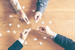 Businessman team work holding two jigsaw. Connecting couple puzzle piece for matching to goals target, success and start up new project in office, top view stock image