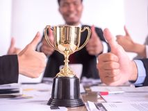 Businessman with teamwork in goal and successful showing trophy and thumb up rewarded for in the office stock photos