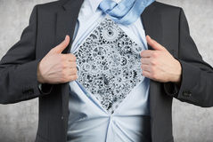 Businessman tearing his shirt with gray gears Royalty Free Stock Photo