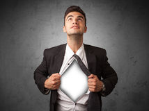 Businessman tearing off his shirt with white copyspace on chest royalty free stock photography