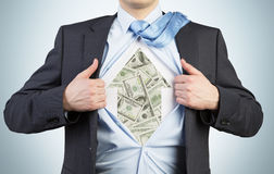 Businessman is tearing the shirt on the chest. Dollar notes under the shirt. Royalty Free Stock Images