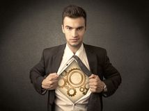 Businessman tearing shirt off and machine cog wheel shows stock photography