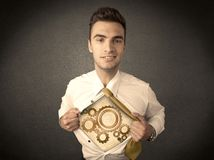 Businessman tearing shirt off and machine cog wheel shows royalty free stock images