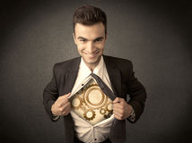 Businessman tearing shirt off and machine cog wheel shows Royalty Free Stock Photo