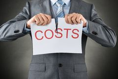 Businessman Tearing The Word Costs On Paper Royalty Free Stock Photography