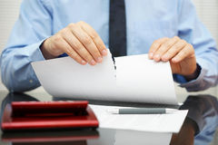 Businessman tears document in office Royalty Free Stock Image