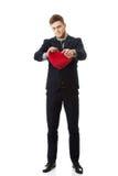 Businessman tears heart shaped pillow. Stock Photos
