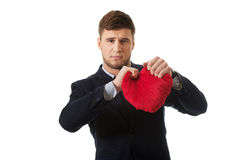 Businessman tears heart shaped pillow. Stock Photo