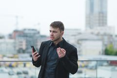 Businessman with a telephone in his hands smokes a cigarette and is angry Stock Photography