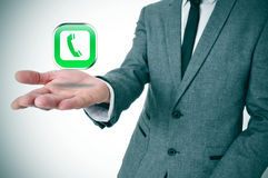 Businessman with a telephone icon in his hand Royalty Free Stock Photos