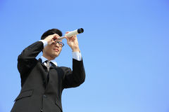 Businessman with telescope looking forward Stock Photos