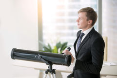 Businessman with telescope. Young happy businessman standing at window with optic telescope, business vision, aspirations, dreaming, thinking of new idea royalty free stock photo