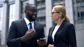 Businessman telling female colleague about useful application in smartphone. Stock photo royalty free stock image
