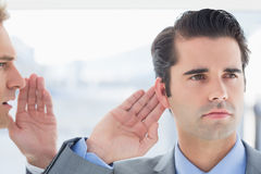 Businessman telling secret to his colleague Royalty Free Stock Photography