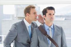 Businessman telling secret to his colleague Stock Image