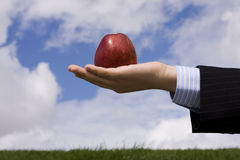 Businessman temptation. A businessman hand holding an apple, as symbol of business temptation royalty free stock photo