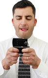 Businessman Text Messaging. A handsome young businessman texting on his cell phone over white stock images