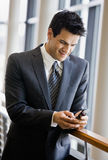 Businessman text messaging on cell phone. In office lobby Royalty Free Stock Photo