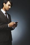 Businessman text messaging on a cell phone Royalty Free Stock Photography